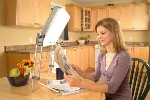 Carex Day-Light being used by a woman to read at the kitchen table
